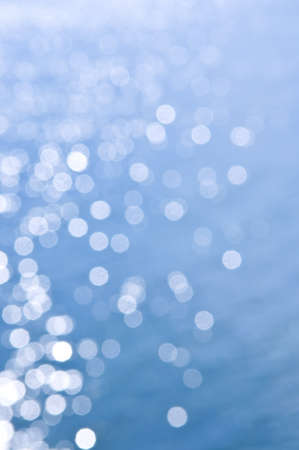 Out of focus bokeh background of blue water with sun reflections photo