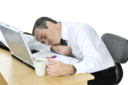 desk: Tired businessman asleep at his desk isolated on white background