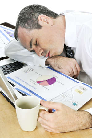 tired: Tired businessman asleep at his desk isolated on white background