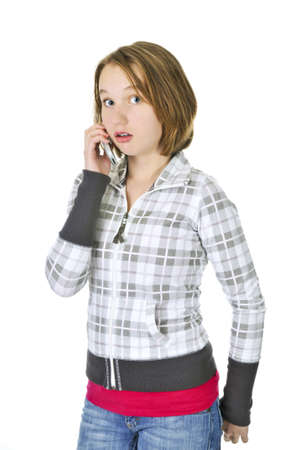 chatty: Teenage girl talking on a cell phone acting surprised isolated on white background Stock Photo