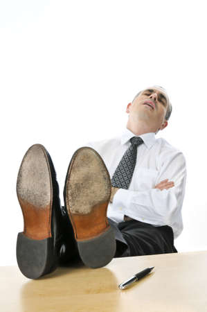 sleeping at desk: Sleeping businessman with feet up on his desk