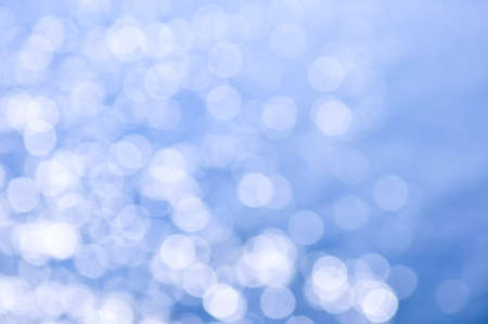 Out of focus bokeh background of blue water with sun reflections. Can be used as Christmas or winter backdrop. photo