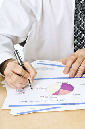 Office worker reviewing generic presentation charts and reports photo