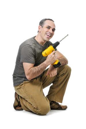 Kneeling happy handyman with his cordless drill