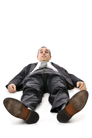 Scared businessman laying down in a suit isolated on white background photo