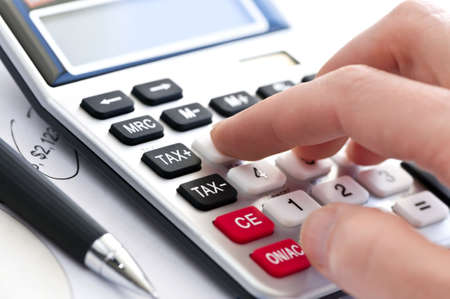 calculating: Typing  numbers for income tax return with pen and calculator