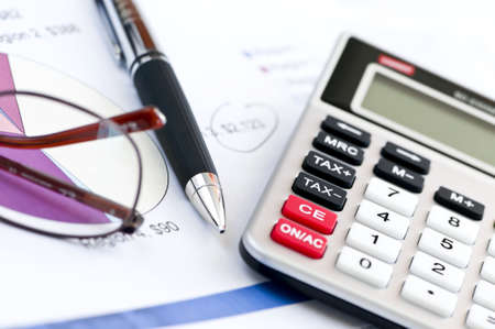 ledger: Calculating numbers for income tax return with glasses pen and calculator Stock Photo