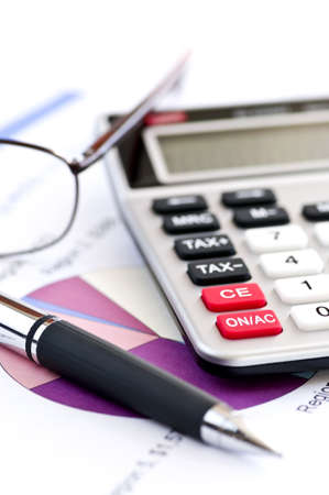 Calculating numbers for income tax return with glasses pen and calculator Stock Photo