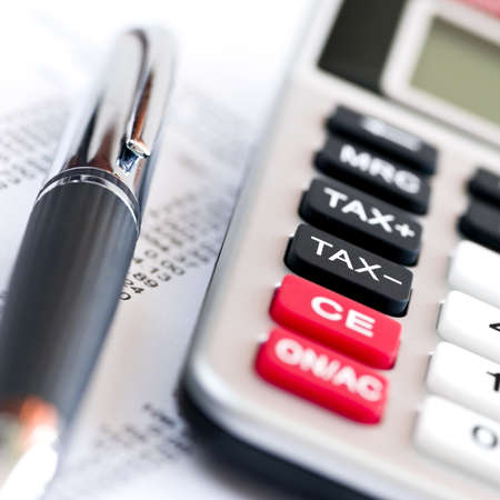 tax return: Calculating numbers for income tax return with pen and calculator Stock Photo