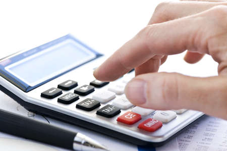 Typing  numbers for income tax return with pen and calculator photo