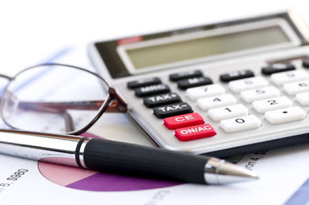 totals: Calculating numbers for income tax return with glasses pen and calculator Stock Photo