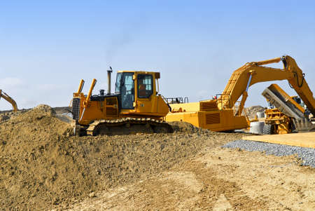 Yellow bulldozer machines digging and moving earth at construction site 스톡 콘텐츠