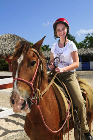 reins: Young girl riding brown horse wearing helmet Stock Photo