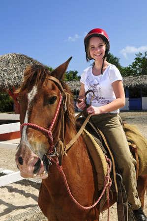 Young girl riding brown horse wearing helmet Stok Fotoğraf
