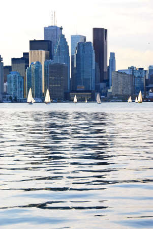 Toronto harbor skyline with skyscrapers and sailboat photo