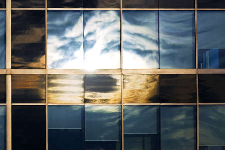 reflect: Reflection of a cloudy sky in glass wall of an office building