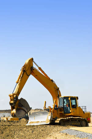 machines: Yellow bulldozer machines digging and moving earth at construction site Stock Photo