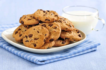 biscuits: Plate of chocolate chip cookies with milk Stock Photo