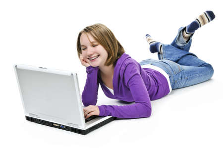 Young girl lying down with laptop computer photo