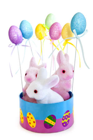 Cute Easter bunny toys in basket with balloons isolated on white background photo