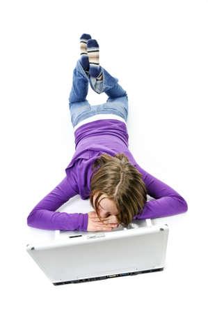 ラップトップ コンピューターで眠りに横たわって疲れている若い女の子 写真素材