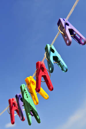 Colorful clothes pegs on line against blue sky photo