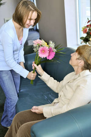 Granddaughter bringing colorful flowers to her grandmother Stock Photo - 4377792