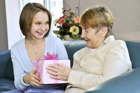 Granddaughter bringing wrapped gift to her grandmother Stockfoto