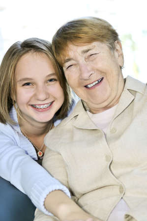 Teen granddaughter hugging grandmother laughing and smiling Stock Photo - 4377789