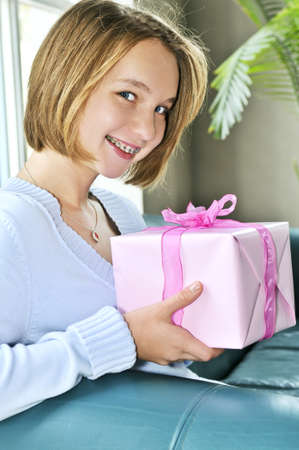 preteen girl: Teenage girl with braces holding wrapped present and smiling