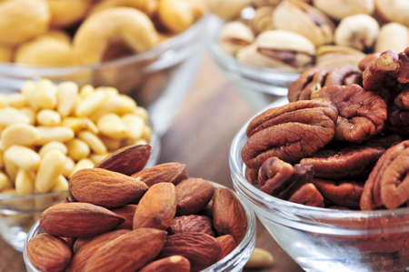 morsels: Many glass bowls of almonds walnuts pistachios and pine nuts