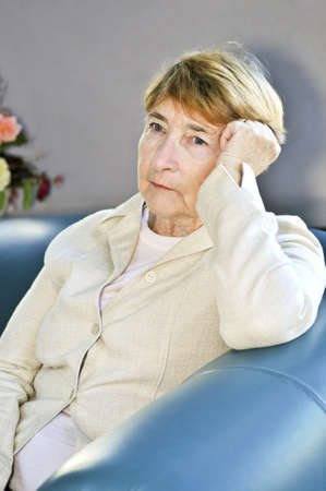 Sad elderly woman sitting on a couch indoors