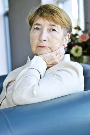 sad old woman: Triste anciana sentada en un sill�n en interiores