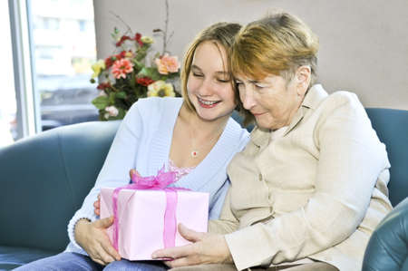 Granddaughter giving a present to her grandmother Stock Photo - 4440494