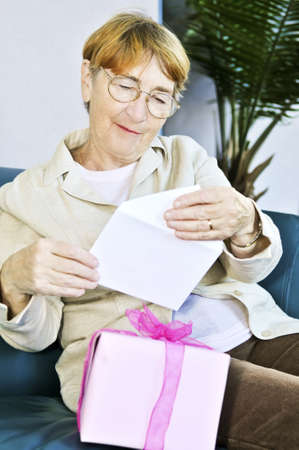 Elderly woman opening birthday card and present Stock Photo - 4440491