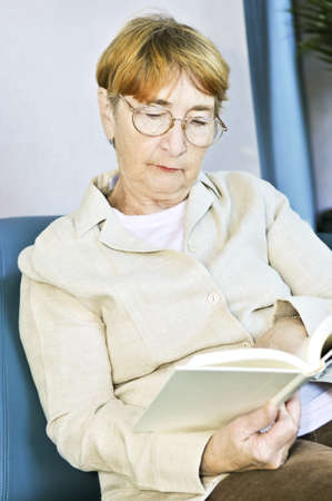 Elderly woman relaxing on couch reading a book photo