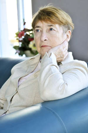 indoors: Sad elderly woman sitting on a couch indoors