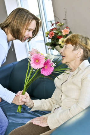 Granddaughter bringing colorful flowers to her grandmother photo