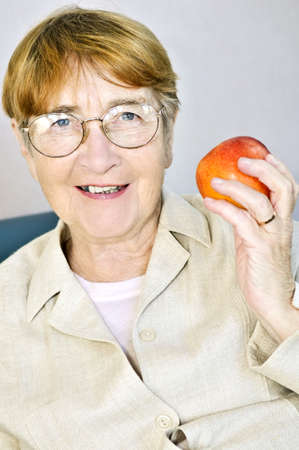 Elderly woman eating healthy holding a nutritious apple photo