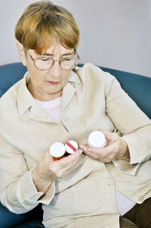 health concern: Elderly woman reading warning labels on pill bottles with medication