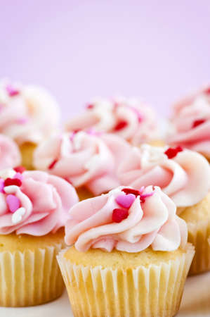 Lots of tasty cupcakes with icing and sprinkles photo