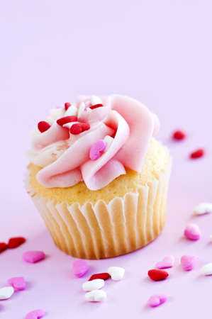 icing sugar: Single cupcake with pink icing and sprinkles