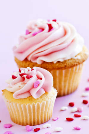 Big and small cupcakes with icing and sprinkles photo