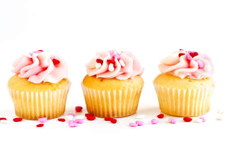 Row of tasty cupcakes with icing and sprinkles photo
