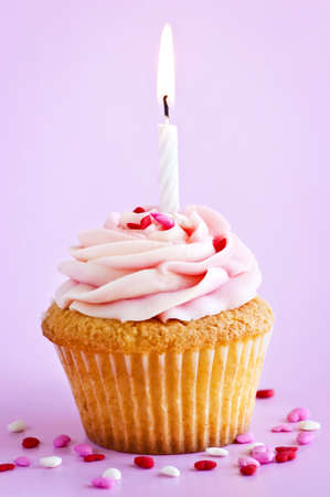 Single cupcake with icing sprinkles and candle photo