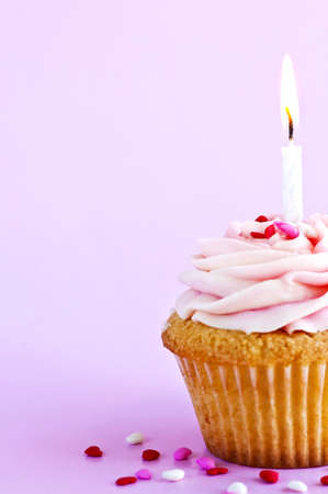 Single cupcake with icing sprinkles and candle Banco de Imagens