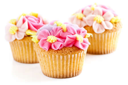 Three tasty cupcakes with icing flowers on white background