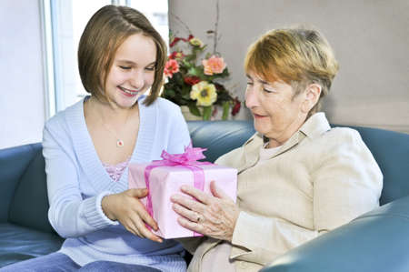 Granddaughter giving a present to her grandmother photo