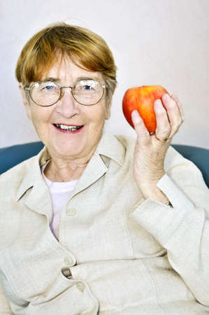 Elderly woman eating healthy holding a nutritious apple Stock Photo - 4484588