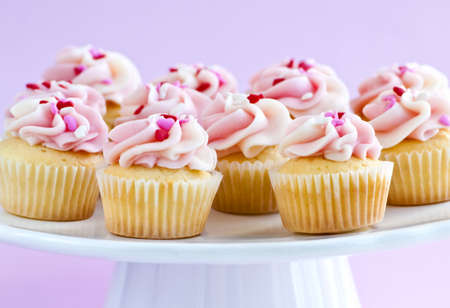 Lots of tasty cupcakes with icing on serving tray Stock Photo